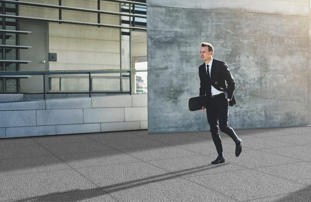 Young businessman with skateboard walking in rush